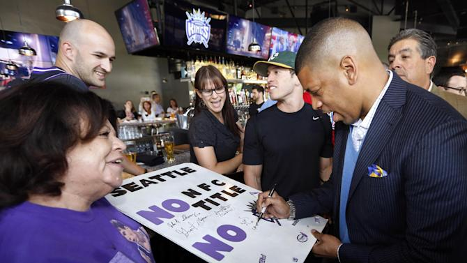 Sacramento Mayor Kevin Johnson, right, autographs a sign for Sacramento Kings fan Gloria Bailey as they celebrate the NBA relocation committees recommendation to reject the application to relocate the Kings basketball team to Seattle in Sacramento, Calif., Monday, April 29, 2013. (AP Photo/Rich Pedroncelli)