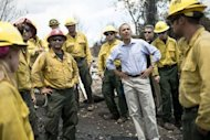 US President Barack Obama pauses with firefighters while touring the Mountain Shadow neighborhood which was burned by wildfires, on June 29 in Colorado Springs, Colorado. US firefighters reported progress Saturday in containing a deadly blaze that has killed two and left hundreds homeless in Colorado, as President Barack Obama hailed their efforts