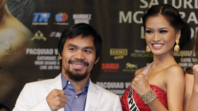 Manny Pacquiao, left, poses for photos with Miss Philippines Janine Tugonon during a news conference, Wednesday, Dec. 5, 2012, in Las Vegas. Pacquiao is scheduled to take on Juan Manuel Marquez in a welterweight boxing match on Saturday. Tugonon is scheduled to compete in the Miss Universe pageant on Dec. 19. (AP Photo/Julie Jacobson)