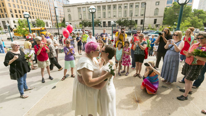 Cody Huston, left, and Tina Cady, both of Madison, embrace after getting married Saturday, June 7, 2014, in Madison, Wis. On Friday a federal judge struck down the state's gay marriage ban. (AP Photo/Andy Manis)