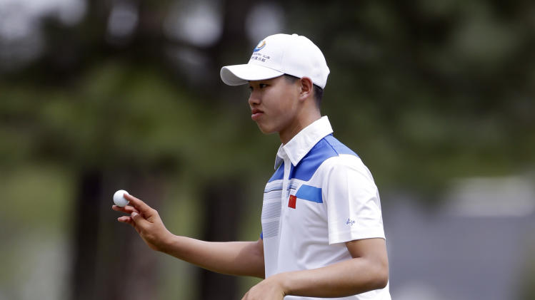 Amateur Guan Tianlang, of China, holds up his ball after putting the eighth green during the first round of the Masters golf tournament Thursday, April 11, 2013, in Augusta, Ga. (AP Photo/David Goldman)