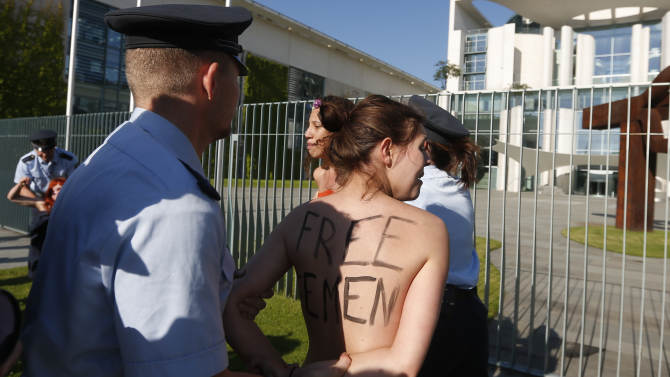 """Activists from the women's movement Femen are being stopped by police officers during a protest in front of the German chancellery ahead of the visit of Tunisian Prime Minister Ali Laarayedh in Berlin, Friday, June 7, 2013. Three topless Femen protesters pleading for Angela Merkel to push for the release of four fellow activists jailed in Tunisia. The women chanted """"Merkel free Femen"""" and two women had painted the names of the activists jailed in Tunisia across their bare chests. Three European Femen demonstrators were arrested last month in Tunis for demonstrating for the release of a Tunisian activist who faces possible charges of public indecency for posting topless photos of herself protesting for women's rights. (AP Photo/Markus Schreiber)"""