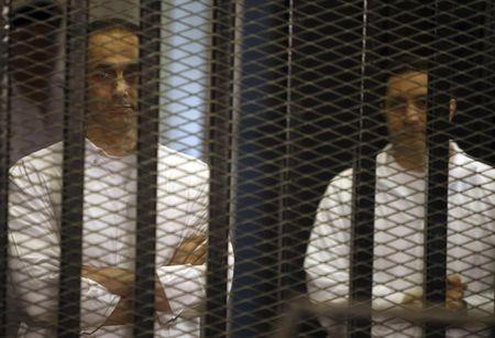 Gamal and Alaa Mubarak, sons of Hosni Mubarak, stand behind bars during their trial at the police academy, on the outskirts of Cairo