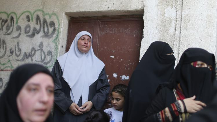 Relatives of the wife of Deif, and his infant son Ali, whom medics said were killed in Israeli air strikes, mourn during their funeral in the northern Gaza Strip