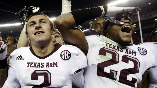 FILE - In this Nov. 10, 2012, file photo, Texas A&M quarterback Johnny Manziel (2) and defensive back Dustin Harris (22) celebrate following their 29-24 win over Alabama in an NCAA college football game in Tuscaloosa, Ala. With the realignment of conferences the past few years, it often means adjusting to a new style of football for teams that are switching. Texas A&M had a rough start, losing losing two of their first four SEC games after leaving the Big 12, but have since moved up to No. 9 in the Top 25 after beating top-ranked Alabama. (AP Photo/Dave Martin, File)