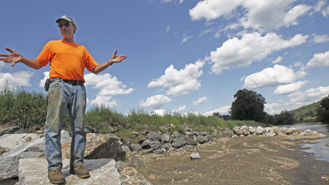 Doug Turner stands along the rebuilt river bank of the Mad River at his farm on Wednesday, Aug. 22, 2012 in Waitsfield, Vt. Devastating floods wrought by Hurricane Irene a year ago inundated farm fields in New York, Pennsylvania and Vermont, wiping out a season's worth of work and setting up fears that the land would be unworkable this year. Since then, a warm spring followed by cold snaps then a blazing, dry summer have added to grower's woes.(AP Photo/Toby Talbot)
