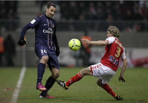 Franck Signorino of Stade Reims fights for the ball with Zlatan Ibrahimovic of Paris St Germain during their French Ligue 1 soccer match in Reims