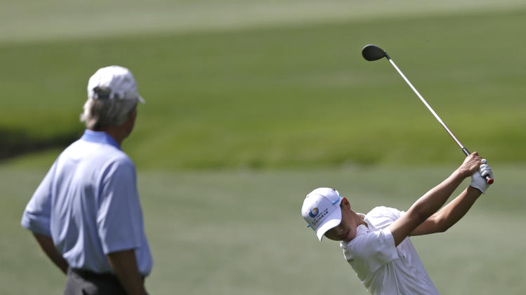 Ben Crenshaw, left watches Amateur Tianlang Guan, of China, hits off a fairway during a practice round for the Masters golf tournament Monday, April 8, 2013, in Augusta, Ga. (AP Photo/David Goldman)