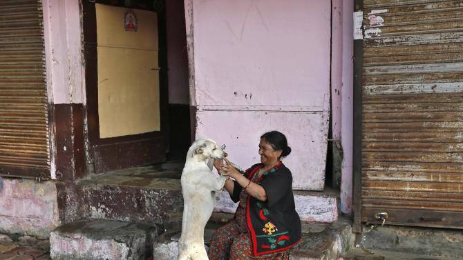A local resident plays with a stray dog outside her house in the western Indian city of Ahmedabad