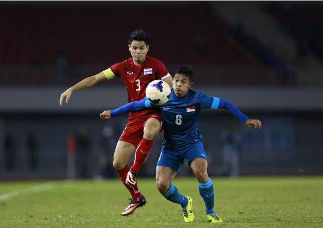 Thailand's Theerathon fights for the ball with Muhammad Hafis of Singapore during soccer semi-final at the 27th SEA Games in Naypyitaw