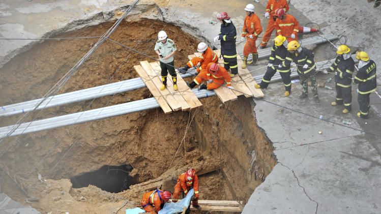 Rescue workers carry out the body of a victim in a road cave-in accident in this picture taken through a security window in Shenzhen