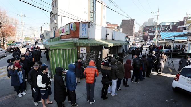 South Koreans wait in line to cast their votes for a presidential election at a polling station in Seoul, South Korea, Wednesday, Dec. 19, 2012. Huge crowds turned out Wednesday to vote in the tight presidential race pitting the son of North Korean refugees against the conservative daughter of a late dictator.  (AP Photo/Yonhap, Shin Jun-hee) KOREA OUT