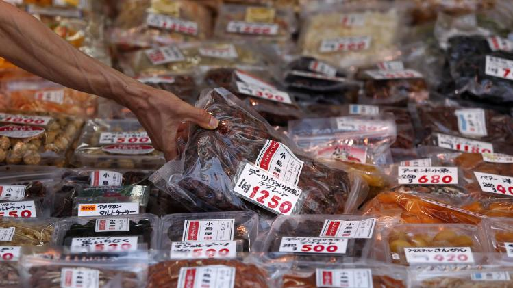 A shopper picks up a pack of dried dates at a food store in Tokyo