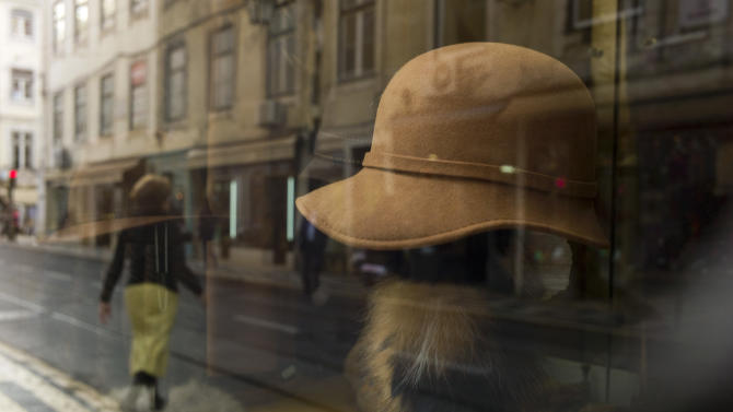 In this photo taken Dec. 21 2012, a women crossing the street is reflected on the window of a women's wear traditional shop in Lisbon's Baixa neighborhood. The downtown district, called the Baixa, was rebuilt after the 1755 quake in what for Portugal is a rare gridiron pattern. Many old-fashioned stores, as well as modern international chains, line the streets. (AP Photo/Armando Franca)