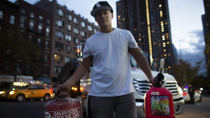 Jose Gil, 27, of Hell's Kitchen, shows his gasoline containers before lining up for fuel at a gas station on 10th Avenue in New York on Saturday, Nov. 3, 2012. Damage from Superstorm Sandy prevented fuel shipments throughout the metropolitan area for days, leading to shortages and long lines expected to continue into the weekend. (AP Photo/John Minchillo)