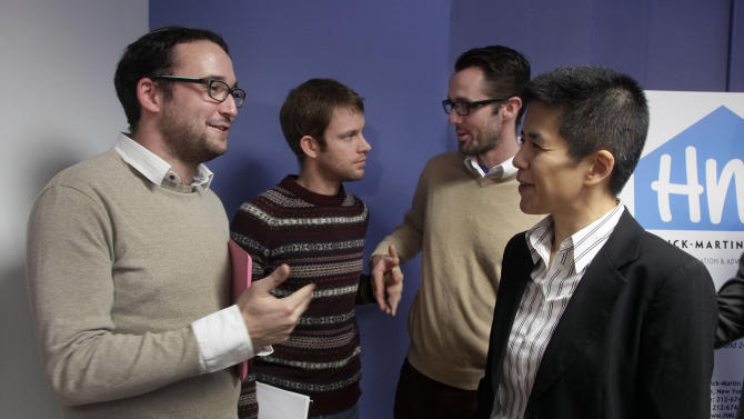 """Chaim Levin, left, talks with Christine Sun, right, deputy legal director for the Southern Poverty Law Center, as Michael Ferguson, background right, stands with his partner Seth Anderson, after a news conference, in New York, Tuesday, Nov. 27, 2012. Levin, of the Crown Heights neighborhood of Brooklyn. NY, and Ferguson, of Salt Lake City, who are gay, are accusing a New Jersey organization of selling """"conversion therapy"""" services promising to make them straight. Instead, they told the news conference that they were subjected to humiliations, including having to strip naked, or taking a baseball bat to effigies of their mothers.  (AP Photo/Richard Drew)"""