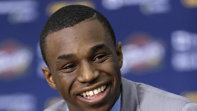 In this June 27, 2014, file photo, Cleveland Cavaliers draft pick Andrew Wiggins smiles during an NBA basketball conference in Independence, Ohio. Two people with knowledge of the deal tell The Associated Press that Minnesota and Cleveland have agreed to a trade that will send All-Star forward Kevin Love to the Cavaliers for Wiggins, Anthony Bennett and a future first-round draft pick. The two people spoke Thursday, Aug. 7, 2014, on condition of anonymity because no official agreement can be reached until Aug. 23, when Wiggins, this year's No. 1 draft pick, becomes eligible to be traded