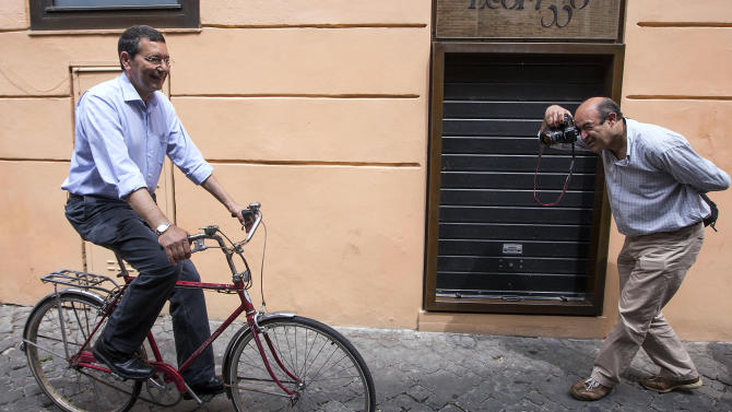 Rome's candidate for mayor rides his bicycle to the polling station as a photographer takes pictures of him, in Rome, Sunday, June 9, 2013. Voters are choosing mayors in Rome and other Italian municipalities in balloting seen as a test of Italian ex-Premier Silvio Berlusconi's political weight, with possible repercussions on the national government. Media mogul Berlusconi campaigned for his center-right party's candidate in Rome, incumbent Gianni Alemanno, who is trying for a second term in a runoff Sunday against former transplant surgeon Ignazio Marino, who is backed by the center-left. (AP Photo/Roberto Monaldo, Lapresse)