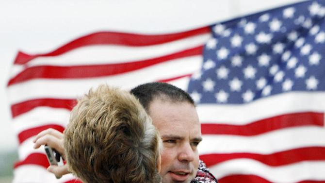 FILE - In this Saturday, April 14, 2012 file photo, Army Pvt. Randy Donovan is hugged by his mother, Twila Donovan, upon arriving at the Crossroads Christian Church in Hutchinson, Kan., for a welcome home party. Donovan was injured by an IED in Afghanistan in November 2011. His injuries included a fractured vertebra in his neck, a broken upper jaw and broken radius in his right elbow. He also had shrapnel wounds to his upper body and two broken vertebrae in his back. Donovan received a Purple Heart. The cost of veterans' benefits and health care peaks decades after a war ends, says Harvard University economist Linda Bilmes. These peaked in 1969 for veterans from World War I and in the 1980s for World War II. They haven't peaked yet for Vietnam veterans. (AP Photo/The Hutchinson News, Lindsey Bauman)