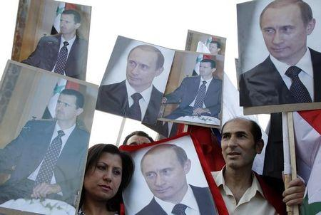 Supporters of Syrian President Bashar al-Assad holds signs with images of al-Assad and Russian President Vladimir Putin after Putin was sworn in as president on Monday, in Damascus