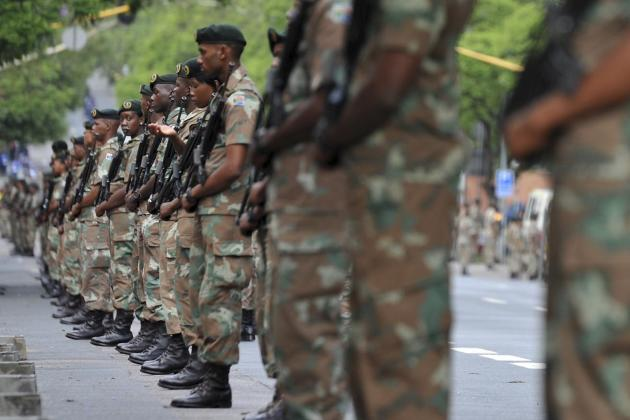Soldiers guard the route that the hearse carrying the body of Nelson Mandela will travel on its way to the Union Buildings in Pretoria