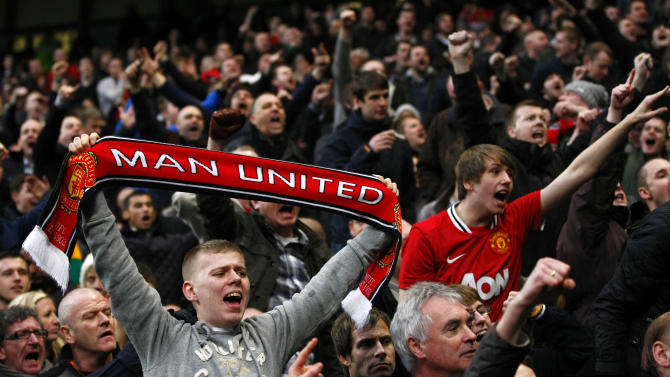 Manchester United fans celebrate after beating Manchester City in their FA Cup third round soccer match at Etihad Stadium, Manchester, England, Sunday, Jan. 8, 2012. (AP Photo/Tim Hales)