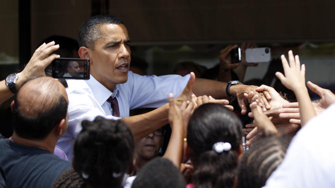 This photo taken Aug. 2, 2012 shows President Barack Obama greeting people outside Lechonera El Barrio, a local restaurant in Orlando, Fla. Undecided voters in swing states hold the key to the presidential election, but there's no obvious recipe for winning them over. Friday's new jobs report, even if dismal, might do little to help challenger Mitt Romney with this group.  (AP Photo/Pablo Martinez Monsivais)
