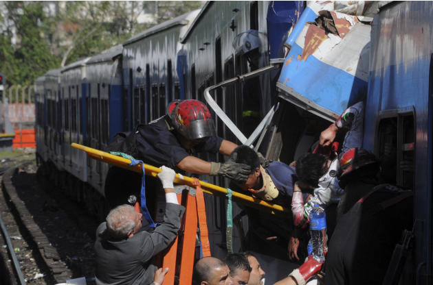Firemen rescue wounded passengers from a commuter train after a collision in Buenos Aires, Argentina, Wednesday Feb. 22, 2012.  A packed train slammed into the end of the line in Buenos Aires' bus