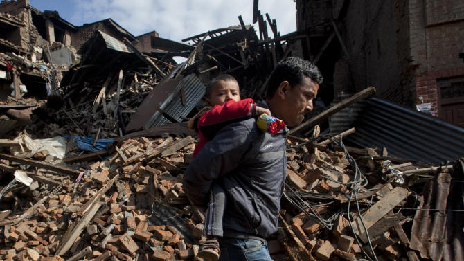 A Nepalese man carries a child as he walks past destroyed buildings that collapsed in Saturday's earthquake, in Bhaktapur, on the outskirts of Kathmandu, Nepal, Monday, April 27, 2015. A strong magnitude earthquake shook Nepal's capital and the densely populated Kathmandu valley on Saturday devastating the region and leaving tens of thousands shell-shocked and sleeping in streets. (AP Photo/Niranjan Shrestha)
