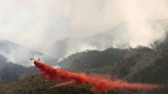 In this June 19, 2012 photo provided by the Colorado National Guard, an aircraft drops a load of fire retardant slurry above the High Park wildfire about 15 miles west of Fort Collins, Colo. The ammonium phosphate dropped from airplanes to slow the spread of raging wildfires can turn a pristine mountain stream into a death zone for trout and some say the retardant has never been proven effective. (AP Photo/Colorado National Guard, John Rohrer)