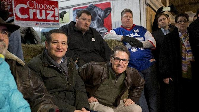 Former Texas Gov. Rick Perry, center, bites his lips as he gets up to introduce Republican presidential candidate, Sen. Ted Cruz, R-Texas, left, at a campaign event at High Point Bulls Oswald Barn, Tuesday, Jan. 26, 2016, in Osceola, Iowa. (AP Photo/Jae C. Hong)