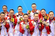 China&#39;s team celebrate on the podium after winning silver in the team free routine final during the synchronised swimming competition at the London 2012 Olympic Games, on August 10, in London