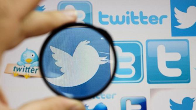 A person holds a magnifying glass over a computer screen displaying Twitter logos