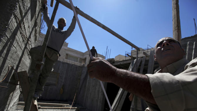 FILE - In this May 4, 2010 file photo, Palestinian men work at a construction site in the east Jerusalem neighborhood of Ramat Shlomo. City of Jerusalem is pushing development in the neighborhood of Ramat Shlomo, a project that has also raised tensions with the U.S. Israel first announced the plans in 2010 during U.S. Vice President Joe Biden's visit to Israel, sparking a diplomatic rift with Washington that took months to mend. (AP Photo/Tara Todras-Whitehill, File)