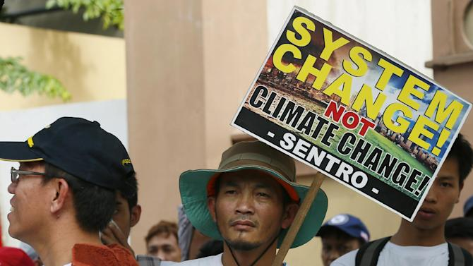 "A protester displays a placard during a rally at the Presidential Palace in Manila, Philippines to coincide with the COP21, United Nations Climate Change Conference in Le Bourget, outside Paris, Monday, Nov. 30, 2015. The protesters are pressing world leaders of industrialized nations and global corporations for ""climate justice"" for their alleged unabated abuse of the environment. (AP Photo/Bullit Marquez)"