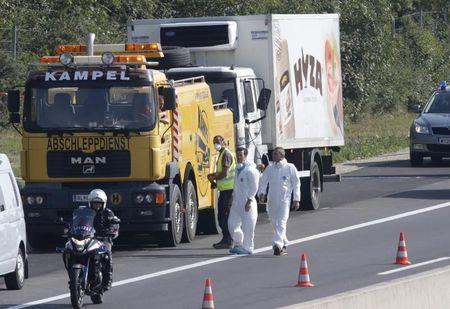 Truck in which up to 50 migrants were found dead is prepared to be towed away on a motorway near Parndorf