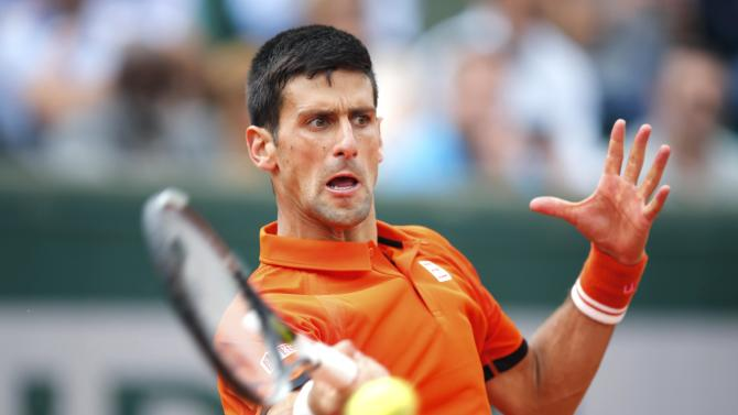Novak Djokovic of Serbia plays a shot to Gilles Muller of Luxembourg during their men's singles match at the French Open tennis tournament at the Roland Garros stadium in Paris