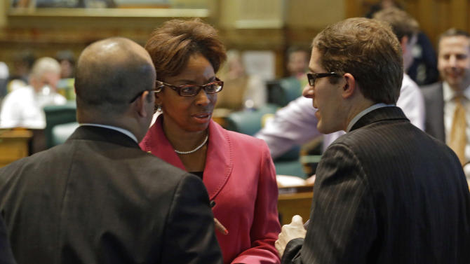 Rep. Rhonda Fields, D-Aurora, center, talks with Rep. Joseph Salazar, left, and House Speaker Mark Ferrandino, right, D-Denver,  about her bill on limiting the size of ammunition  magazines at the Capitol in Denver on Friday, Feb. 15, 2013. Kicking off a long, emotional debate about guns, Colorado lawmakers clashed Friday over setting limits on the size of ammunition magazines, a proposal in a package of Democratic bills responding to mass shootings at a suburban Denver movie theater and a Connecticut elementary school.(AP Photo/Ed Andrieski)