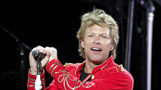 """FILE - This July 27, 2011 file photo shows singer Jon Bon Jovi performing during Bon Jovi's """"Open Air Tour"""" show at Estadio Olympico, in Barcelona, Spain. Avon Products Inc. announced Monday, July 2, 2012, that the 50-year-old rock star is the company's newest celebrity fragrance partner. He'll appear in ads for both Unplugged for Her and Unplugged for him.  The company said the inspiration for both scents is the unique feeling one has listening to a favorite song. The goal is """"an emotional connection."""" The women's version, which will be available through Avon representatives and online in October, is a floral oriental perfume, and the men's is a woody floral musk fragrance. It will go on sale in November. (AP Photo/Job Vermeulen, file)"""