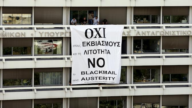 Employees of the Ministry of Finance and National Economy stand by a banner unfolded from a balcony of the Finance Ministry in Athens