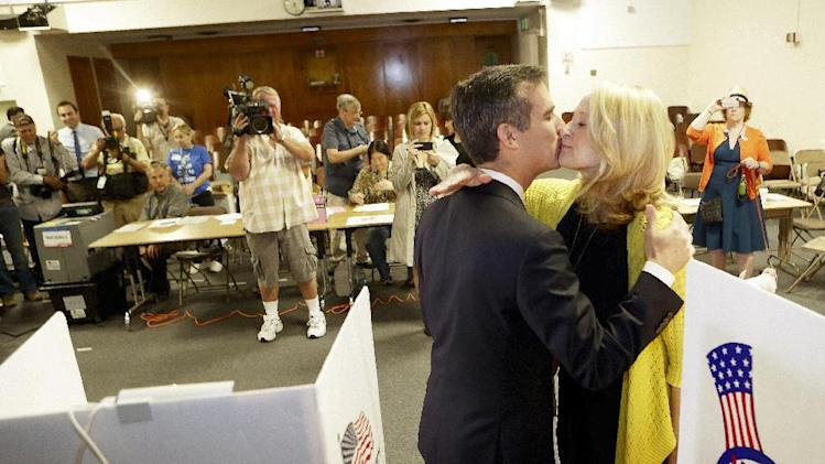 Los Angeles Mayoral candidate Eric Garcetti gets a kiss from his wife Amy Wakeland, as they vote early Tuesday morning, May 21, 2013, in Los Angeles. Garcetti faces Wendy Greuel in the mayoral runoff election.   (AP Photo/Damian Dovarganes)