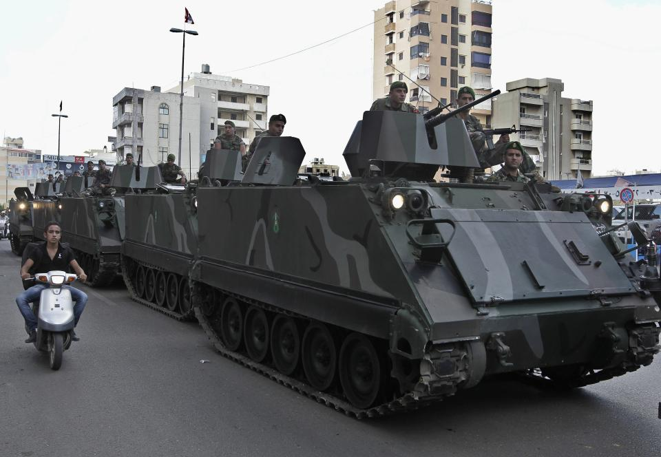 Lebanese army soldiers patrol in armored vehicles in a southern suburb of Beirut, Lebanon, Monday, Sept. 23, 2013. Hundreds of Lebanese soldiers and policemen begun deploying in Hezbollah strongholds south of Beirut after officials said they had reached a deal with the militant group to return a government presence to the area. (AP Photo/Bilal Hussein)