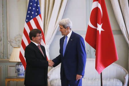 U.S. Secretary of State Kerry shake hands with Turkish Foreign Minister Davutoglu in Paris
