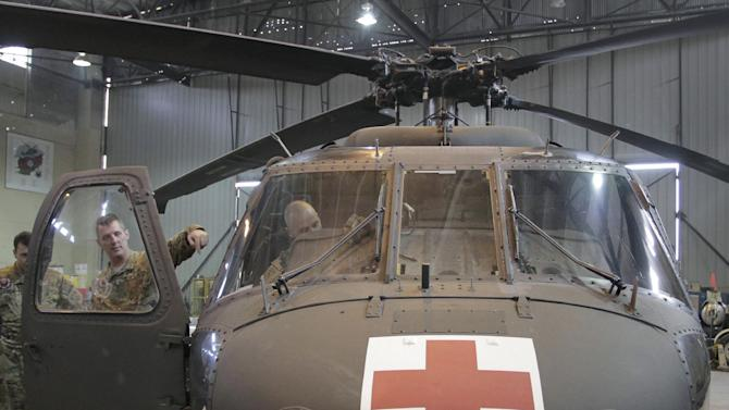 In this Saturday, Jan. 28, 2012 photo, U.S. Maj. Graham Bundy, center left, medevac commander from Sussex, Wisc., points to the inside of a U.S. medevac helicopter in a hangar at the U.S. Bagram air field, north of Kabul, Afghanistan. About 20 U.S. lawmakers have written to military officials inquiring about a Sept. 18, 2011 incident, when it took a medevac unit 59 minutes to get U.S. Army Spec. Chazray Clark, a 24-year-old combat engineer from Detroit, to a hospital in southern Afghanistan after receiving a call that a roadside bombing severed three of his limbs. Clark did not survive. The incident has revived a debate over whether medevac helicopters should have their own guns.  (AP Photo/Musadeq Sadeq)