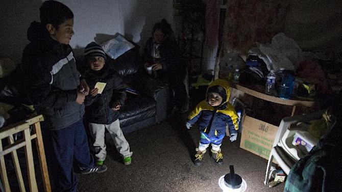 Living through another night of possibly freezing temperatures, Michael Pineda, fifteen months old, stands bundled up near a battery operated lantern in his home without power or heat in the Rockaway Park neighborhood in the Queens borough of New York, Thursday, Nov. 8, 2012, in the wake of Superstorm Sandy. From left is his brother Mario Pineda, 12, Walter Rivera, 5, and center in deep shadow is their mother Fatima Pineda. (AP Photo/Craig Ruttle)