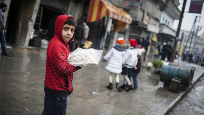 A child sells bread in the streets of Aleppo, Syria, Saturday, Jan. 5, 2013. The revolt against President Bashar Assad that started in March 2011 began with peaceful protests but morphed into a civil war that has killed more than 60,000 people, according to a recent United Nations recent estimate. (AP Photo/Andoni Lubaki)