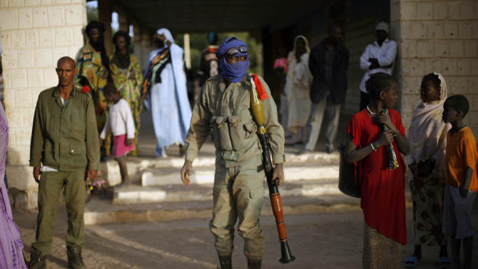 A Malian soldier walks in the street after arriving in a convoy at the military base in Timbuktu, Mali, Saturday Feb. 2, 2013. French President Francois Hollande visited the fabled city for two hours, twenty days after the start of operation Serval. (AP Photo/Jerome Delay)