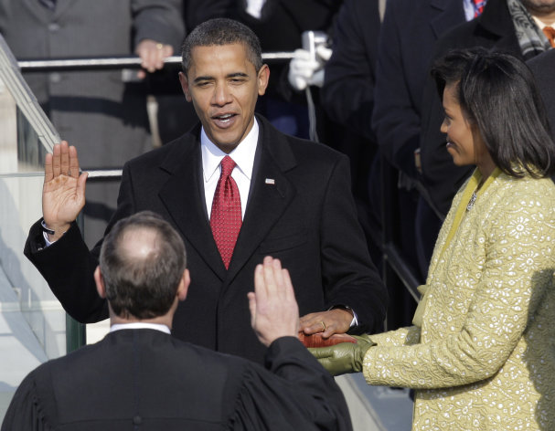 FILE - Barack Obama, left, joined by his wife Michelle, takes the oath of office from Chief Justice John Roberts to become the 44th president of the United States at the U.S. Capitol in Washington, D.C., in this Jan. 20, 2009 file photo. Obama is putting a symbolic twist on a time-honored tradition, taking the oath of office for his second term with his hand placed not on a single Bible, but two, one owned by Martin Luther King Jr. and one by Abraham Lincoln. (AP Photo/Jae C. Hong, File)