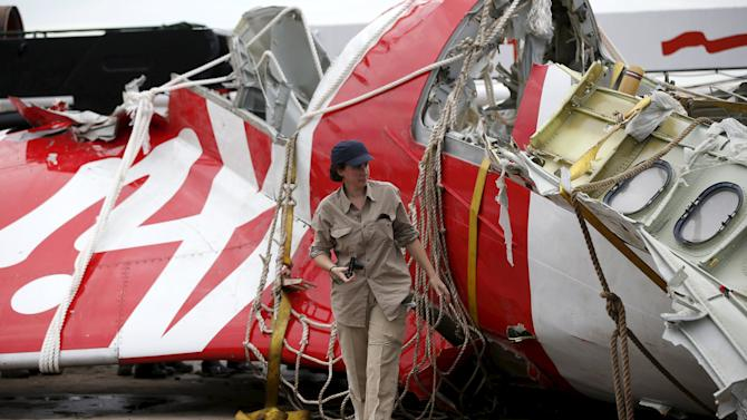File photo of an Airbus investigator walking near part of the tail of the AirAsia QZ8501 passenger plane in Kumai Port, near Pangkalan Bun