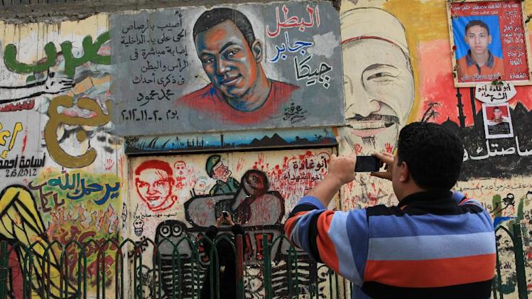 Egyptians document revolutionary graffiti in Tahrir Square, Cairo, Egypt, Friday, Jan. 25, 2013. Egyptian opposition protesters are gathering in Cairo's Tahrir Square to mark the second anniversary of the uprising that toppled Hosni Mubarak's autocratic regime. (AP Photo/Thomas Hartwell)